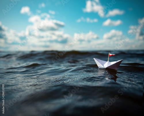 Kleines Papierschiff in großen Wellen