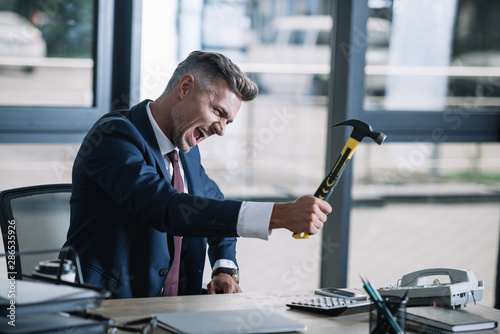 selective focus of angry businessman holding hammer near phone on table Canvas Print