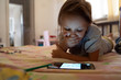 girl child lies at home on the bed and uses a smartphone