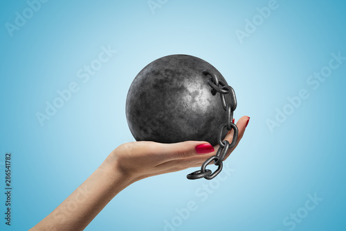 Photo Side closeup of woman's hand facing up and holding black ball and chain on light blue gradient background