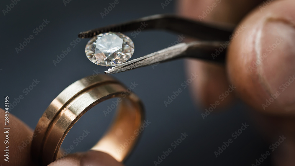 Fototapeta Jeweler craftsman selects a gem for a future gold ring, close-up