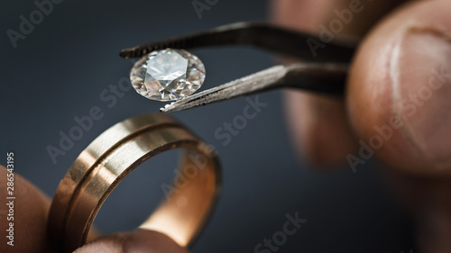 Photo Jeweler craftsman selects a gem for a future gold ring, close-up