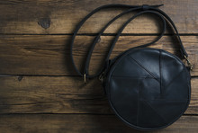 Black Leather Female Bag On Wooden Background, Top View