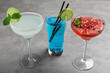 Glasses of tasty refreshing cocktails on grey table