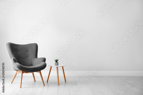 Obraz na plátne Stylish room interior with comfortable armchair near light wall, space for text