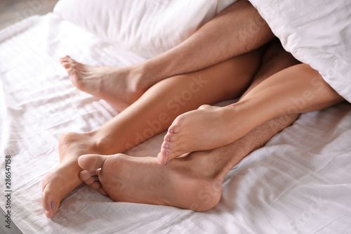 Obraz Passionate young couple having sex on bed, closeup of legs - fototapety do salonu