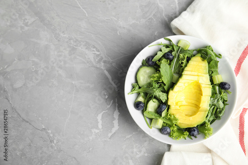 Fotografie, Obraz  Delicious avocado salad with blueberries in bowl on grey marble table, flat lay