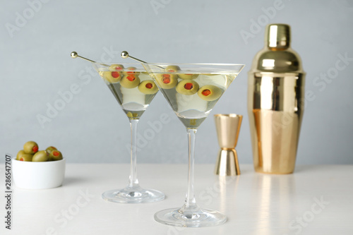 Fotografía  Glasses of Classic Dry Martini with olives on wooden table against grey backgrou