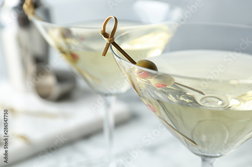 Cuadros en Lienzo Glasses of Classic Dry Martini with olives on table, closeup