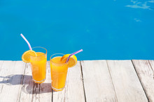 Refreshing Cocktails Near Outdoor Swimming Pool On Sunny Day. Space For Text