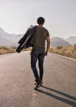 Unrecognizable Young Man Walking On The Road With His Black Jacket To The Mountains