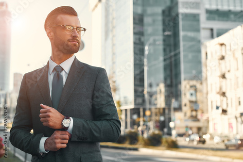 Photo Portrait of young and handsome bearded man in full suit adjusting his sleeve and