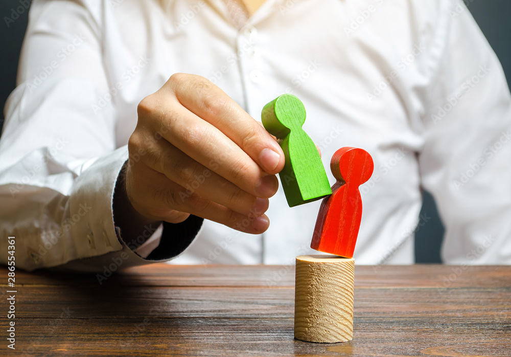 Fototapeta A person replaces a red human figure with a green one. firing staff. Head Offset. Business optimization, replacement of key employees with loyal ones. Change of power. Anti corruption. system recovery