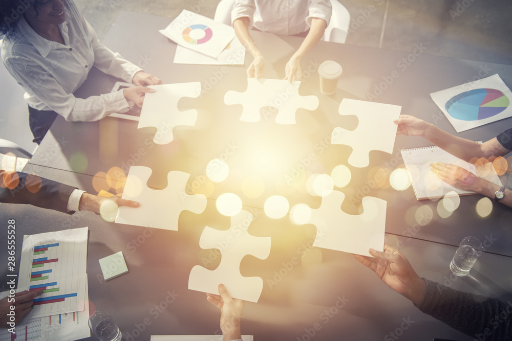 Fototapeta Business people join puzzle pieces in office. Concept of teamwork and partnership. double exposure with light effects