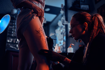 Attractive focused tattoo artist is creating new tattoo on young woman's leg at dark tattoo studio.