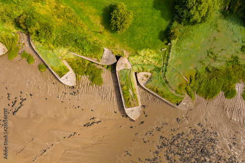 Aerial drone view of silt filled abandoned ships on the banks on a muddy river Tapéta, Fotótapéta