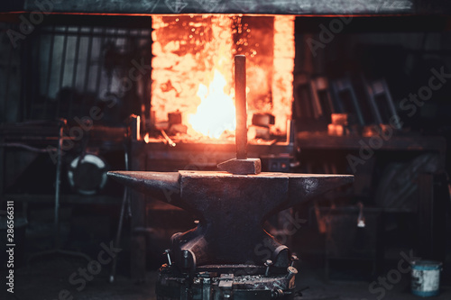 Cuadros en Lienzo Hammer on anvil at dark blacksmith workshop with fire in stove at background