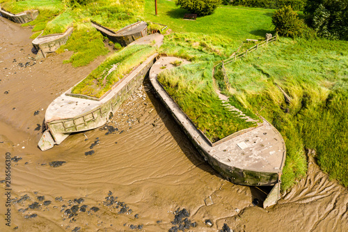Valokuva  Aerial drone view of silt filled abandoned ships on the banks on a muddy river