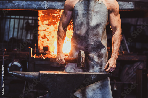 Muscular blacksmith in protective apron at his workshop with hammer in his hands Wallpaper Mural