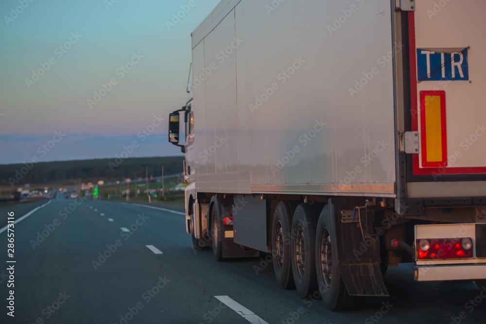 Fototapeta truck goes on highway on sunset