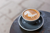 Gray cup of cappuccino with latte art on the table in cafe. Tasty cappuccino with horse latte. Top view.