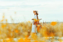 Young Pretty Woman Wearing A Hat Looking At The Sky On A Field With Her Yellow Bicycle.