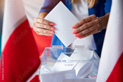Fotografie, Obraz Woman putting her vote to ballot box. Poland political elections
