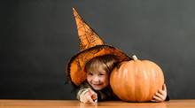 Child With Pumpkin. Little Boy In Witch Hat With Halloween Pumpkin Pointing To You. Trick Or Treat. Preparation Halloween Holiday. Happy Halloween. Halloween Party. Boy Dressed Up Trick Or Treating.