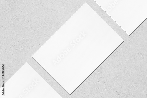 Fotografía  Close up of three empty white rectangle poster mockups lying diagonally with soft shadow on neutral light grey concrete background
