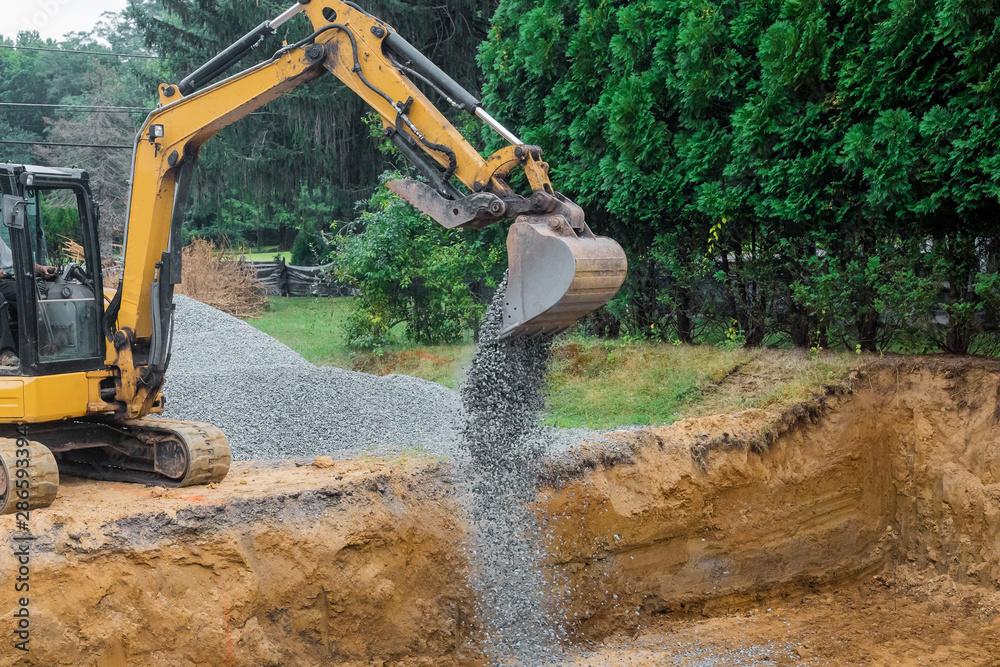 Fototapeta A yellow excavator bucket shovel moving stones gravel of foundation on a construction site