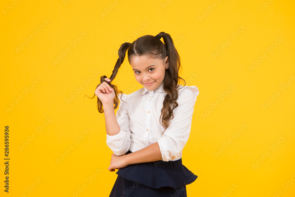 Fototapety, obrazy: Modest hairstyle. Cute little schoolchild winding hairstyle around her finger on yellow background. Fashion girl with long ponytail hairstyle in formal style. Small kid styling hairstyle for school