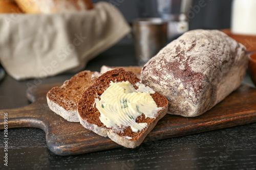 Fototapeta Sliced bread with butter on dark table obraz