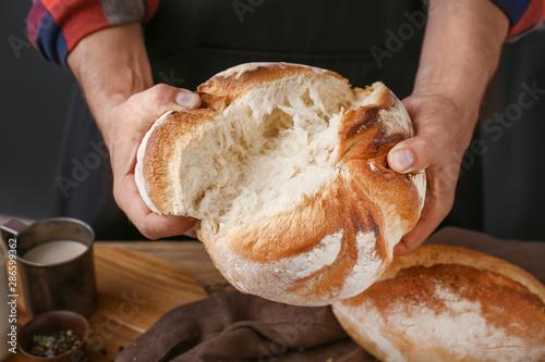Woman breaking fresh bread, closeup