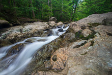 Silky Water Rushing Over Eroded Rocks With Green Forest In Background