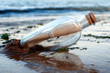 canvas print picture - Asking for assistance, optimism and survivor desperation to contact the world conceptual idea with a message in a glass bottle with a cork washing away on sandy beach with the ocean in the background