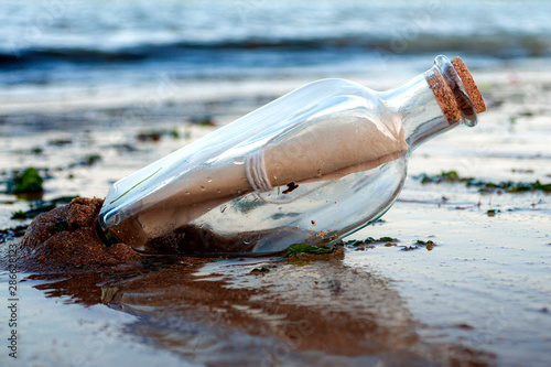 Obraz Asking for assistance, optimism and survivor desperation to contact the world conceptual idea with a message in a glass bottle with a cork washing away on sandy beach with the ocean in the background - fototapety do salonu