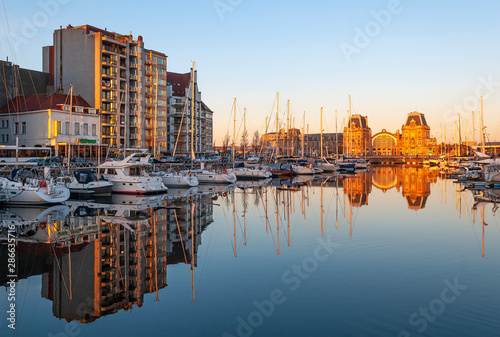 Aluminium Prints Northern Europe Reflection of the yacht sailing ships and Ostend (Oostende in Flemish) city train station in the harbor at sunset, Ostend, Belgium.