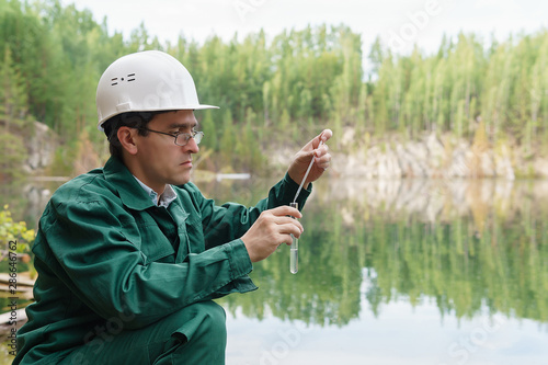 industrial ecologist takes a sample of water from lake at the site of a flooded Canvas-taulu