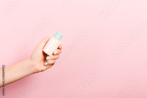 Photographie Female hand holding cream bottle of lotion isolated