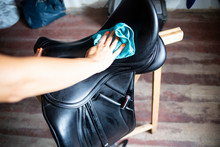 Cleaning And Maintenance Of The Saddle. The Woman Rider Cares For The Saddle