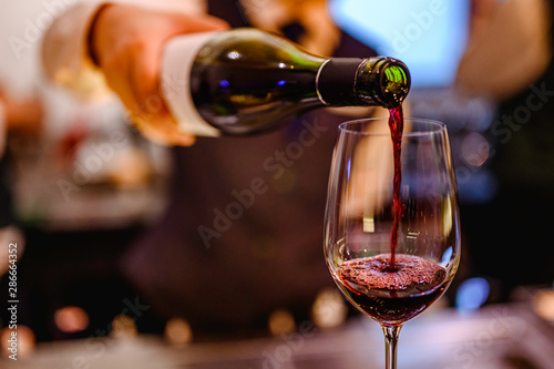 Fotografia  Pouring glass of red wine from a bottle.