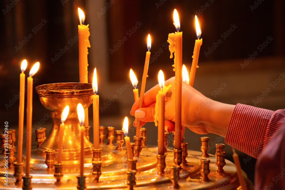 Fototapety, obrazy: Woman hand picking candle in church, traditional religious scene