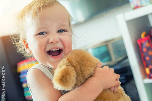 Cute adorable caucasian blond toddler boy having fun, laughing and hugging soft puppy toy indoors Wallpaper Mural