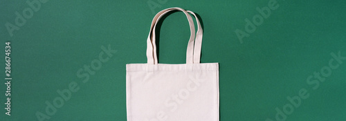 Fototapeta Canvas tote bag canvas and linen fabric bags with drawstring on green background with copy space. Top view. Zero waste, plastic free concept. Eco friendly shopper. obraz