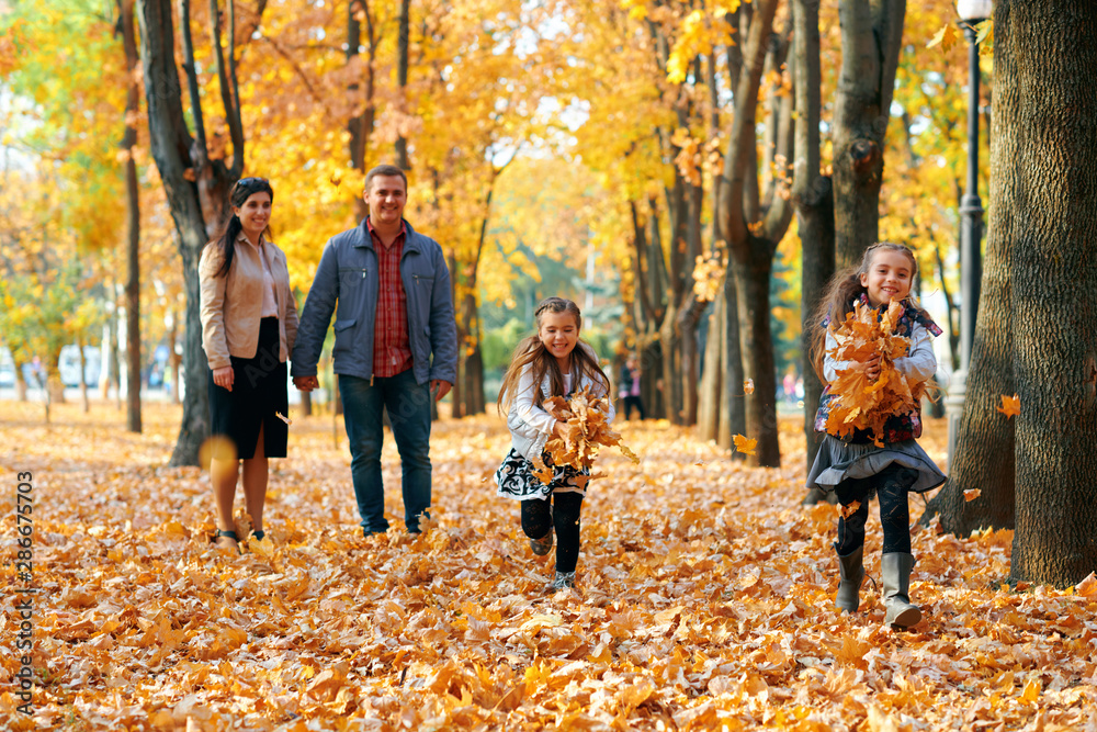 Fototapety, obrazy: Happy family having holiday in autumn city park. Children and parents posing, smiling, playing and having fun. Bright yellow trees and leaves