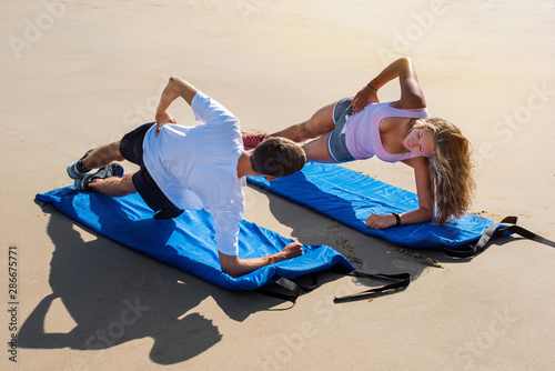 young couple doing pilate on the sunny beach Canvas Print