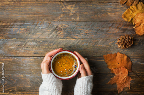 Młoda caucasian kobiety dziewczyna w trykotowym białym pulowerze trzyma w ręka kubku z świeżo parzoną kawą z apetycznej crema suchymi pomarańczowymi żółtymi liśćmi na starzejącym się drewnianym kuchennym stole. Przytulna jesienna atmosfera