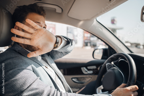 Valokuvatapetti Young driver hides his face and looks scared because of dangerous traffic situation that could cause sar accident