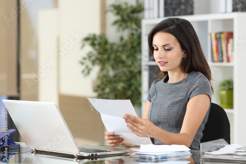Fotomural Serious office worker reading a paper letter