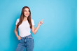 Portrait of pretty youth pointing at copy space looking at ads wearing white t-shirt denim jeans isolated over blue background